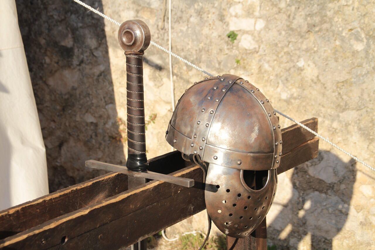 Średniowieczny hełm oraz miecz na stojaku